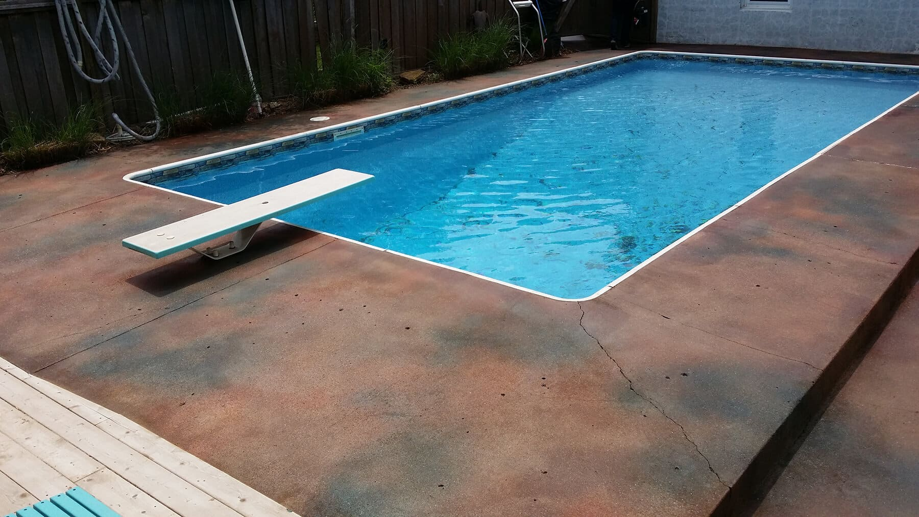 Pool deck of concrete in Kansas City, with diving board