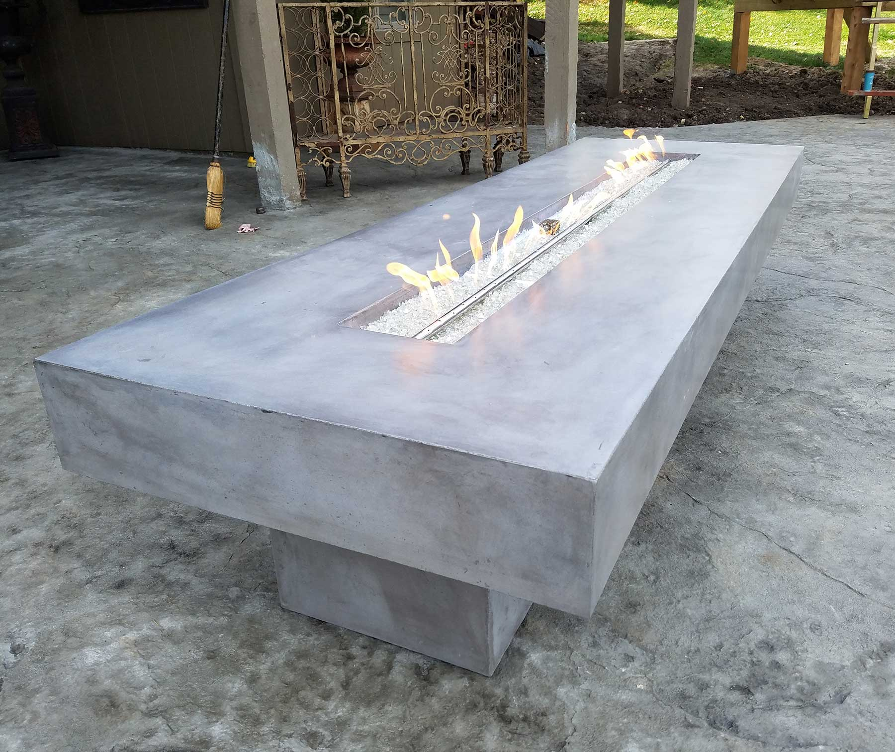 gray concrete gas-powered firepit, with white rock