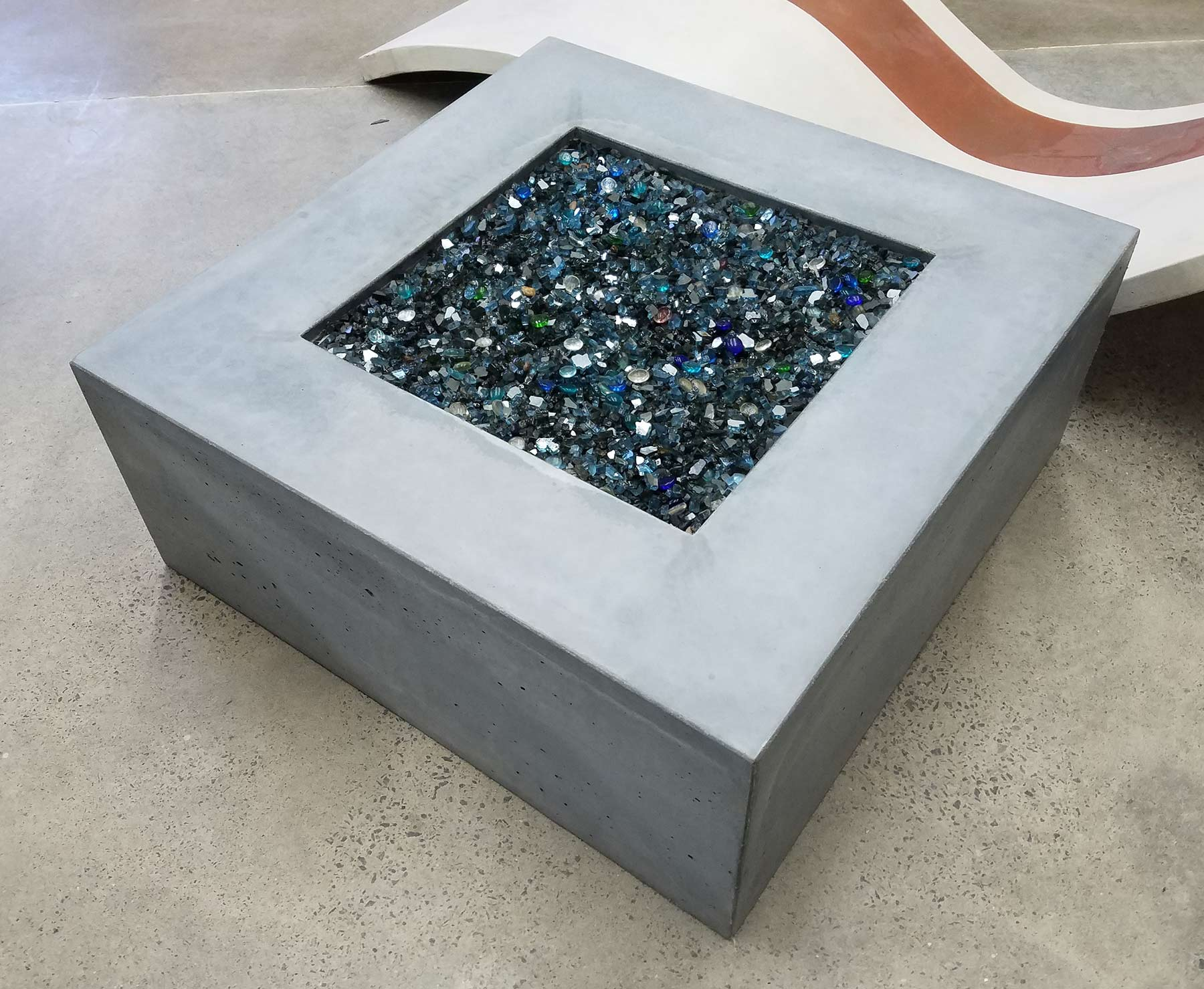 square concrete firepit with translucent stones, gas powered