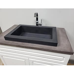 concrete vessel sink installed in decorative cabinet