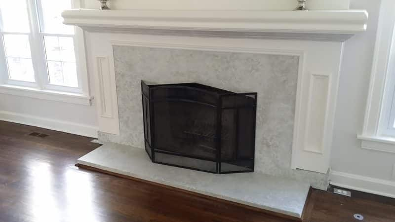 white and gray marble appearance fireplace surround made of concrete